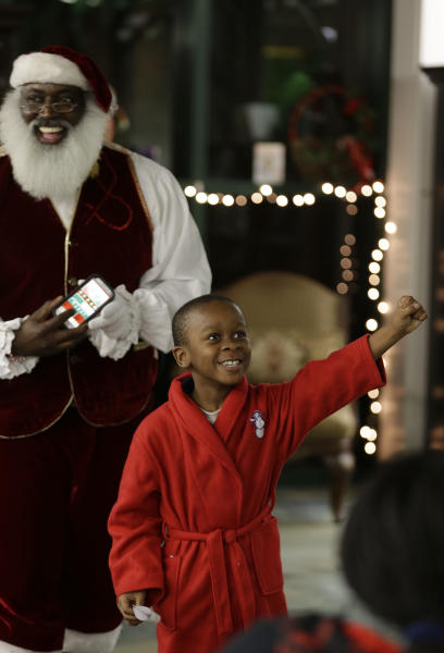 """In this Tuesday, Dec. 17, 2013 photo, Dee Sinclair, who bills himself as the """"Real Black Santa"""" smiles as Paris Allen, 7, reacts after passing a naughty or nice test in Atlanta. (AP Photo/John Bazemore)"""