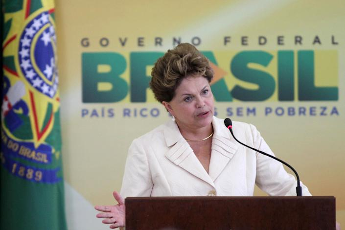 "Brazil's President Dilma Rousseff speaks during a ceremony where she announced an economic stimulus package at Planalto presidential palace in Brasilia, Brazil, Wednesday, June 27, 2012. The program announced by Rousseff focuses on a wide array of government purchases, from backhoes to motorcycles to military equipment. Rousseff says the government will use stimulus packages ""without restriction"" as Brazil is hit by the crisis in Europe and hobbled by slowing domestic consumer demand. (AP Photo/Eraldo Peres)"