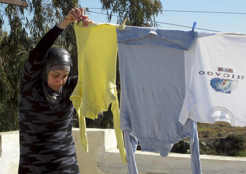 """In this Sunday, Feb. 3, 2013 photo, Palestinian Suraia Burnat, 42, wife of the Palestinian co-director of """"Five Broken Cameras"""" hangs washing on the rooftop of their home in the West Bank village of Bilin. In an unusual move in the mostly conservativeArab society, her husband Emad filmed her and their children -- even as they argued -- hoping to show audiences how a normal Palestinian family coped during years of struggle against Israel's separation barrier. (AP Photo/Diaa Hadid)"""