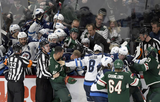 Minnesota Wild and Winnipeg Jets players scuffle at the Jets' bench during the third period of an NHL hockey game Friday, Nov. 23, 2018, in St. Paul, Minn. The Wild won 4-2. (AP Photo/Hannah Foslien)