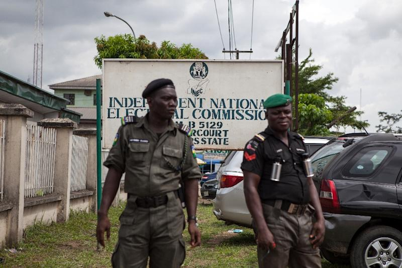 Police officers stand outside the Independent National Electoral Commission (INEC) offices in the oil hub of Port Harcourt