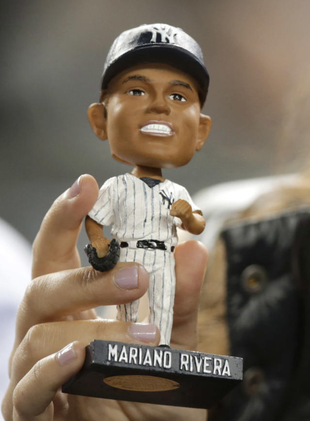 A fan displays a Mariano Rivera bobblehead doll during the New York Yankees' baseball game against the Tampa Bay Rays, Tuesday, Sept. 24, 2013, in New York. (AP Photo/Kathy Willens)