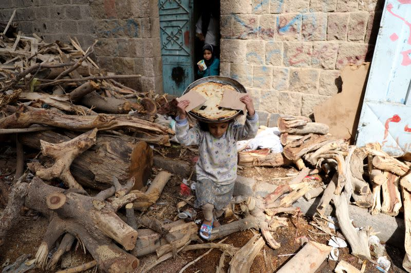 A girl carries bread baked in a wood-fired oven in Sanaa
