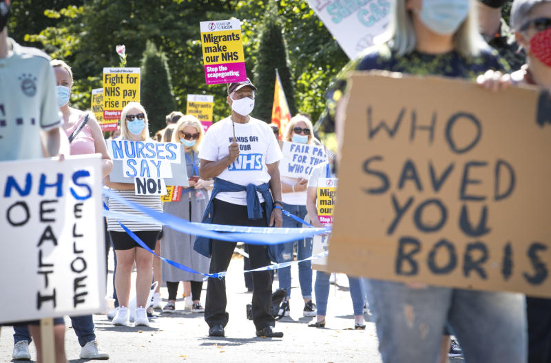 National Health Service (NHS) workers pose with placards, during a socially distanced demonstration as part of a national protest over pay, in Glasgow, Scotland, Saturday Aug. 8, 2020. Nationwide protests on Saturday are calling for government to address what they claim is many years of reduced wages, and are calling for a voice in plans for public sector pay increases. (Jane Barlow/PA via AP)