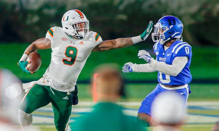 Miami Hurricanes tight end Brevin Jordan (9) carries the football as Duke Blue Devils safety Marquis Waters (0) closes in the first half at Wallace Wade Stadium Saturday, Dec. 5, 2020.