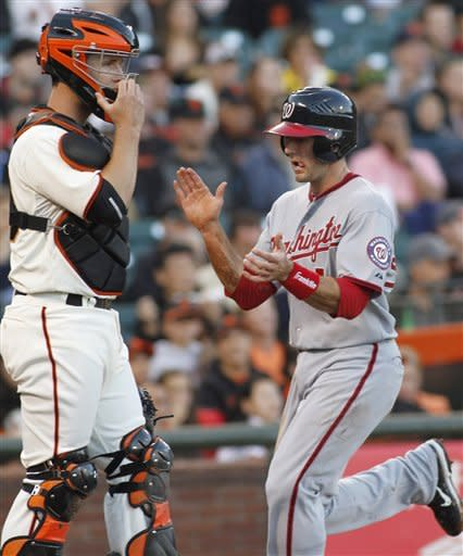 Washington Nationals' Steve Lombardozzi claps his hands as he scores in front of San Francisco Giants' Buster Posey during the first inning of a baseball game, Monday, Aug. 13, 2012 in San Francisco, Calif. (AP Photo/George Nikitin)