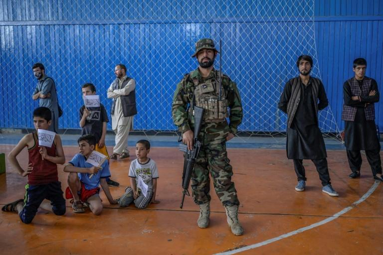 A Taliban fighter stands as youths wait to show off their skills at an Kabul gym -- an event organised for the visit of Afghanistan's new sports chief Bashir Ahmad Rustamzai (AFP/BULENT KILIC)
