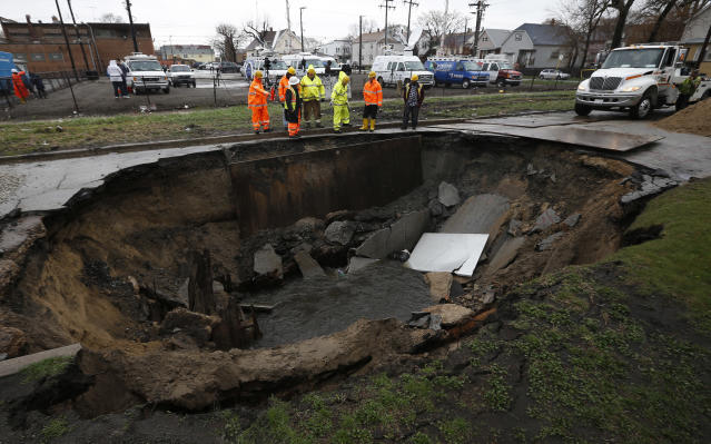 Workers look into a sinkhole caused by a broken water main in Chicago, Illinois, April 18, 2013. Heavy rains and flooding brought havoc to the Chicago area on Thursday, shutting major expressways, delaying commuter trains for hours, cancelling flights, flooding basements and closing dozens of suburban schools. On the city's South Side, a sinkhole opened up on a residential street, swallowing three cars, according to Officer Mike Sullivan of the Chicago Police Department. One person was hospitalized with non-life-threatening injuries. REUTERS/Jim Young (UNITED STATES - Tags: ENVIRONMENT TPX IMAGES OF THE DAY) - RTXYR8X