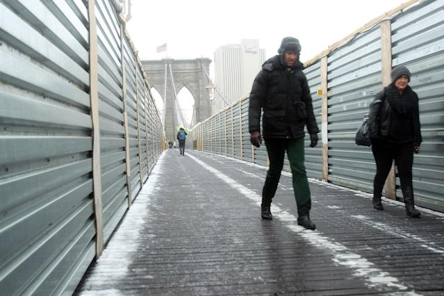 NEW YORK, NY - FEBRUARY 08: Two people carefully walk across the Brooklyn Bridge in the snow and sleet in the early hours of a major winter storm on February 8, 2013 in New York City. New York City and much of the Northeast is expected to get a foot or more of snow through Saturday afternoon with possible record-setting blizzard conditions expected in Boston, Massachusetts. Heavy snow warnings are in effect from New Jersey through southern Maine. (Photo by Spencer Platt/Getty Images)