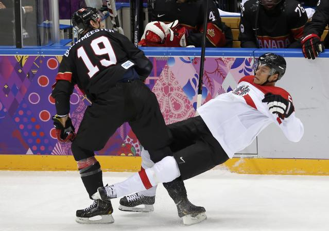 Canada's Jay Bouwmeester (L) hits Austria's Thomas Raffl during the first period of their men's preliminary round ice hockey game at the 2014 Sochi Winter Olympics, February 14, 2014. REUTERS/Jim Young (RUSSIA - Tags: OLYMPICS SPORT ICE HOCKEY)