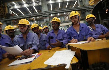 Employees check papers during their meeting after their lunch break inside the heavy electrical manufacturing unit of Larsen & Turbo in Mumbai