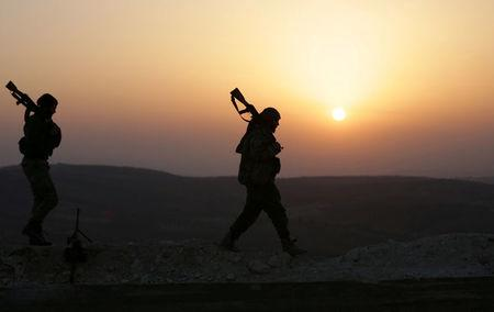 Turkish-backed Free Syrian Army fighters walk as the sun sets in Eastern Afrin countryside, Syria, February 6, 2018. REUTERS/Khalil Ashawi