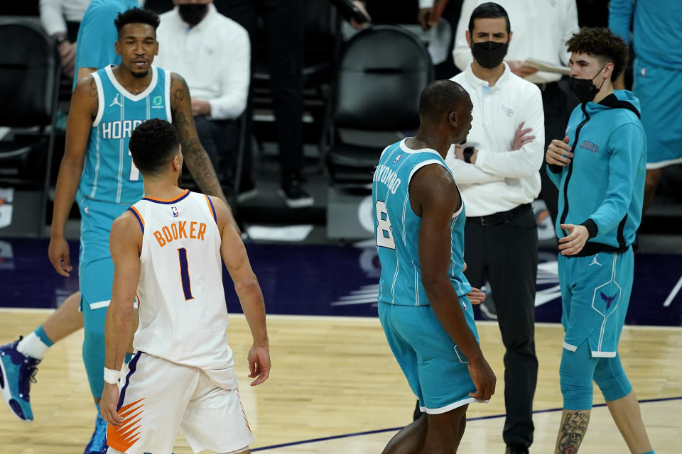 Phoenix Suns guard Devin Booker (1) has words with Charlotte Hornets guard LaMelo Ball, right, during the second half of an NBA basketball game, Wednesday, Feb. 24, 2021, in Phoenix. Booker was given a technical foul for the confrontation. (AP Photo/Matt York)