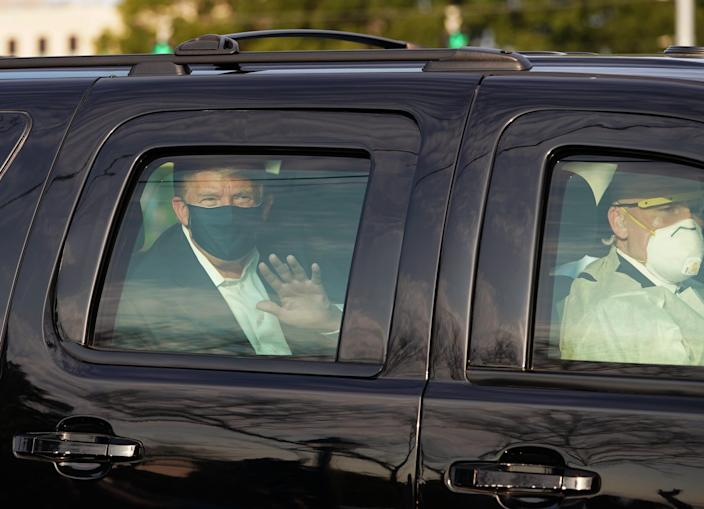 President Trump waves from the back of an SUV in a motorcade outside of Walter Reed in Bethesda, Md., on Oct. 4, 2020.