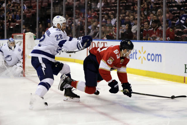 Tampa Bay Lightning's Kevin Shattenkirk (22) checks Florida Panthers' Evgenii Dadonov (63) as goalkeeper Andrei Vasilevskiy, left, watches during the second period of an NHL hockey game, Tuesday, Dec. 10, 2019, in Sunrise, Fla. (AP Photo/Luis M. Alvarez)