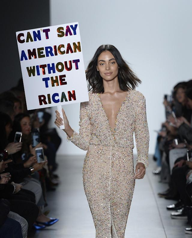 "<p>A model carries a sign that reads ""Can't say American without the Rican"" during the runway show for Stella Nolasco. (Photo: Getty Images) </p>"
