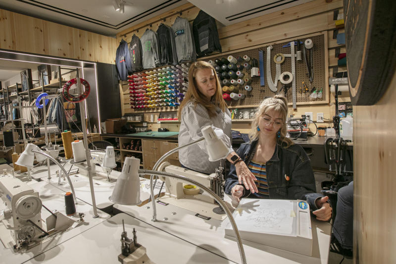 In this June 14, 2019, photo Sue Ceccarelli, left, Vice President of Retail Operations for Levi Strauss & Co.. talks with with tailor Aly Reinert in the Levi's Tailor Shop, in the Levi's store, in New York's Times Square. Levi Strauss & Co.'s new flagship in Manhattan's Time Square features larger dressing rooms with call buttons and tailors who can add trims and patches to customers' jeans. (AP Photo/Richard Drew)