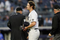 New York Yankees starting pitcher Gerrit Cole reacts after umpire Bill Miller, right, checked him for foreign substances after Cole pitched in the top of the third inning of a baseball game, Tuesday, June 22, 2021, at Yankee Stadium in New York. Home plate umpire Brian Knight is at left. (AP Photo/Kathy Willens)
