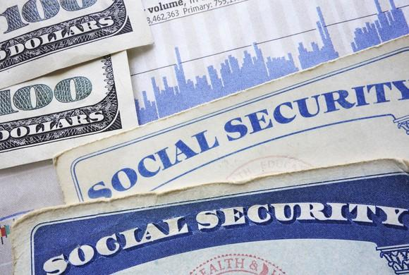 portions of social security cards and hundred dollar bills visible on a flat surface
