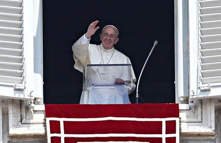 Pope Francis waves as he leads the Angelus prayer from the window of the Apostolic palace in Saint Peter's Square at the Vatican