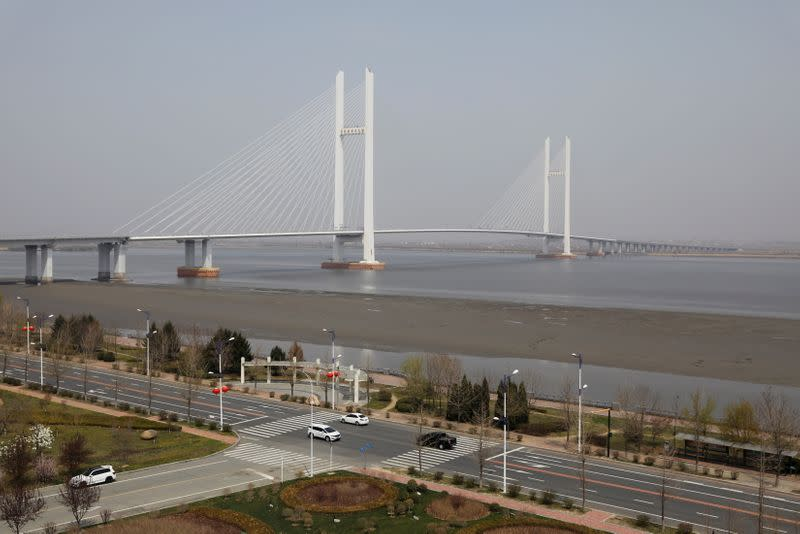 Cars travel past the New Yalu River Bridge designed to connect China's Dandong New Zone and North Korea's Sinuiju, in Dandong
