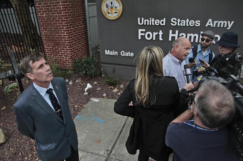Robert Reeg, far left, a retired firefighter who was injured while responding to the Sept. 11 attacks, stands aside listening as Fairben, third from right, who lost his son Keith in the attacks, holds a press briefing on Monday, Oct. 15, 2012, outside Fort Hamilton Army base in Brooklyn, N.Y. Military installations in New York, New Jersey, Massachusetts and Maryland are welcoming families of 9/11 victims this week to watch pretrial hearings in Cuba for five men charged in the terrorist attacks via closed-circuit television. (AP Photo/Bebeto Matthews)