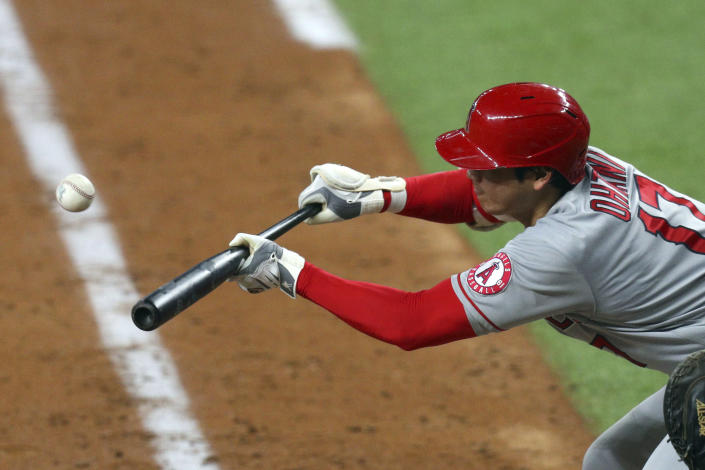 Los Angeles Angels starting pitcher Shohei Ohtani bunts his way on base against the Texas Rangers in the sixth inning during a baseball game on Monday, April 26, 2021, in Arlington, Texas. (AP Photo/Richard W. Rodriguez)