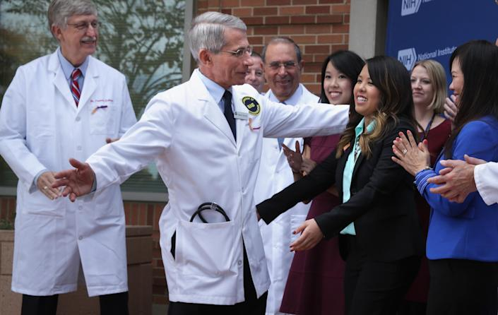 Director of the National Institute of Allergy and Infectious Diseases Anthony Fauci (2nd L) hugs Nina Pham (5th L), the nurse who was infected with Ebola from treating a patient (AFP Photo/Alex Wong)