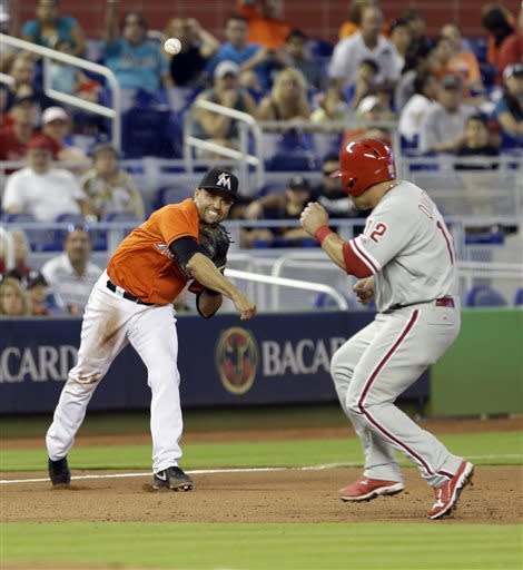 Miami Marlins third baseman Placido Polanco, left, throws to first base after fielding a ground ball hit as Humberto Quintero (12) heads to third base during the fifth inning of a baseball game in Miami, Sunday, April 14, 2013. Quintero was safe at third base. The Phillies won 2-1. (AP Photo/Alan Diaz)