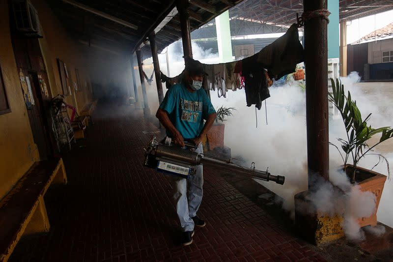 A worker fumigates a school being used as a shelter as Storm Iota approaches, in Choluteca