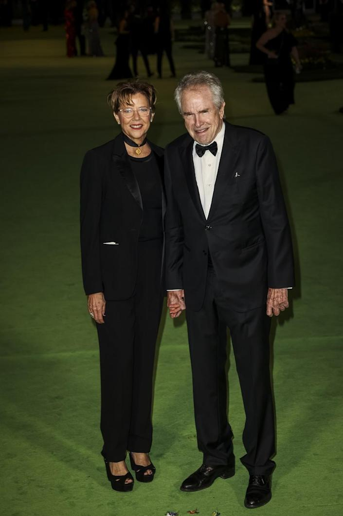 A woman in a black suit and a man in a black tuxedo posing on a green carpet