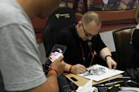 <p>Comic book artist Adi Granov drawing while a fan looks on at the Singapore Toy, Game and Comic Convention (STGCC) 2018 (PHOTO: Abdul Rahman Azhari/Yahoo Lifestyle Singapore) </p>