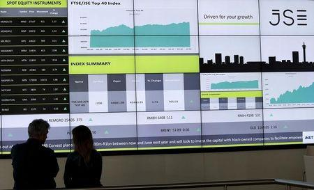 People chat  in front of an electronic board displaying movements in major indices at the Johannesburg Stock Exchange building in Sandton Johannesburg