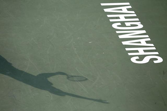 The shadow of Jo-Wilfried Tsonga of France is cast on the court as he serves to Pablo Andujar of Spain during their singles match at the Shanghai Masters tennis tournament at Qizhong Forest Sports City Tennis Center, in Shanghai, China, Wednesday, Oct. 9, 2013. (AP Photo/Eugene Hoshiko)