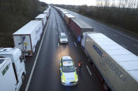 Police patrol along the M20 motorway where freight traffic is halted whilst the Port of Dover remains closed, in Ashford, Kent, England, Tuesday, Dec. 22, 2020. Trucks waiting to get out of Britain backed up for miles and people were left stranded at airports as dozens of countries around the world slapped tough travel restrictions on the U.K. because of a new and seemingly more contagious strain of the coronavirus in England. (Andrew Matthews/PA via AP)