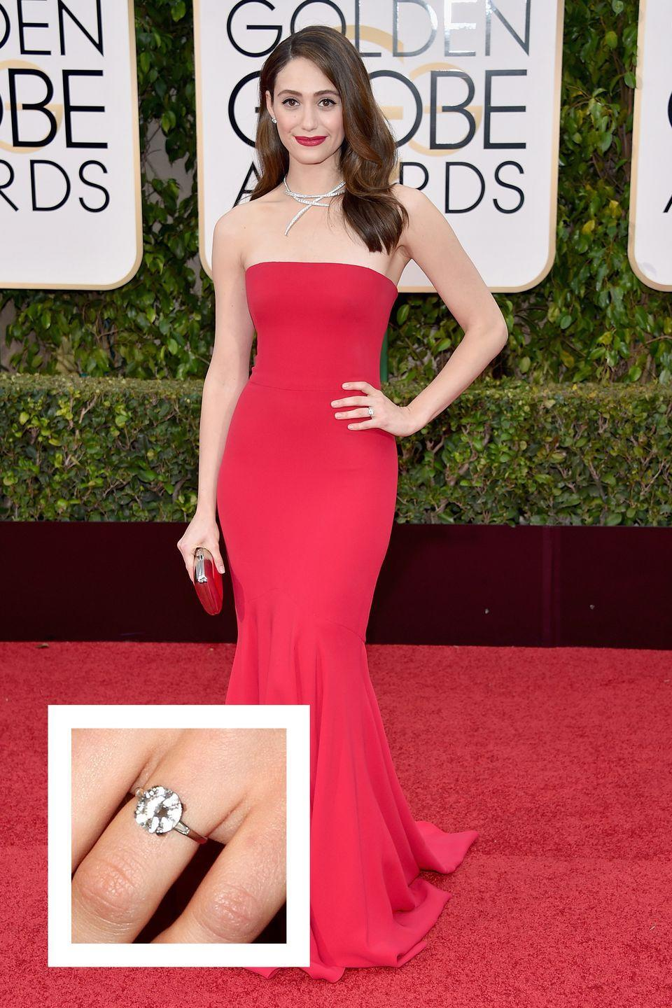 """<p>Rossum's now-husband Sam Esmail proposed with an elegant vintage ring that has truly stood the test of time: it dates back to Paris in the 1920s, <a href=""""https://www.brides.com/story/emmy-rossum-vintage-engagement-ring-details"""" rel=""""nofollow noopener"""" target=""""_blank"""" data-ylk=""""slk:Brides reports."""" class=""""link rapid-noclick-resp""""><em>Brides</em> reports.</a> Rossum's round solitaire ring is flanked by two baguettes on a platinum band. </p>"""