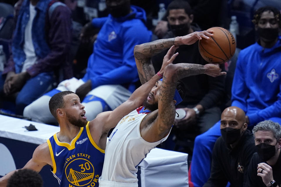 New Orleans Pelicans forward Brandon Ingram tries to control the ball under pressure from Golden State Warriors guard Stephen Curry (30) in the first half of an NBA basketball game in New Orleans, Tuesday, May 4, 2021. (AP Photo/Gerald Herbert)