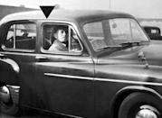 <p>A man is photographed sitting in the passenger seat of a car while the face of his deceased mother appears in the backseat behind him.</p>