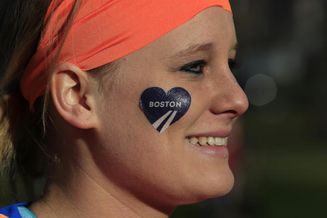 Mackenzie Petermeier, of Baxter, Iowa, who will be a guide for a blind runner, waits to board a bus in Boston to the starting line in Hopkinton, Mass., for the 118th Boston Marathon Monday, April 21, 2014. (AP Photo/Matt Rourke)