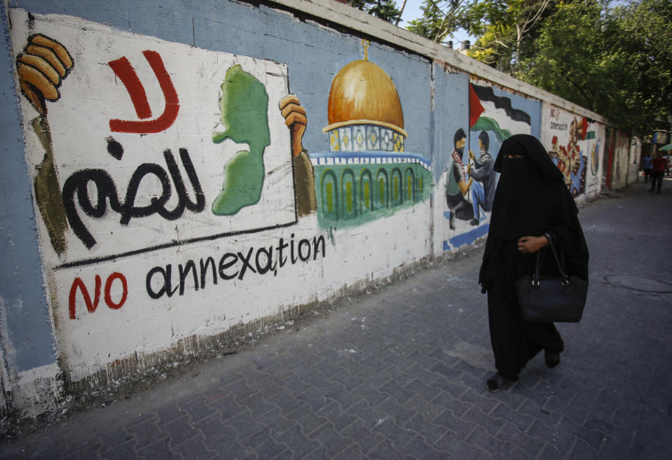 GAZA, PALESTINE - 2020/07/14: A Palestinian woman walks past a protest mural of Israel's plan to annex parts of the Israeli-occupied West Bank, in Rafah in the southern Gaza Strip. (Photo by Yousef Masoud/SOPA Images/LightRocket via Getty Images)