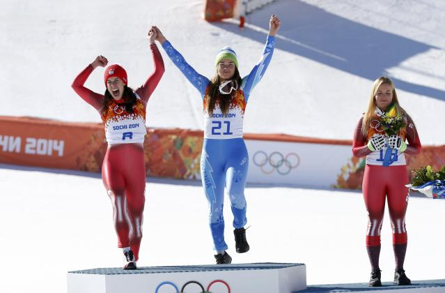 Winners Dominique Gisin of Switzerland (L) and Tina Maze of Slovenia (C) and Switzerland's third-placed Lara Gut celebrate on podium after the women's alpine skiing downhill event during a flower ceremony at the 2014 Sochi Winter Olympics at the Rosa Khutor Alpine CenterFebruary 12, 2014. REUTERS/Leonhard Foeger (RUSSIA - Tags: OLYMPICS SPORT SKIING)