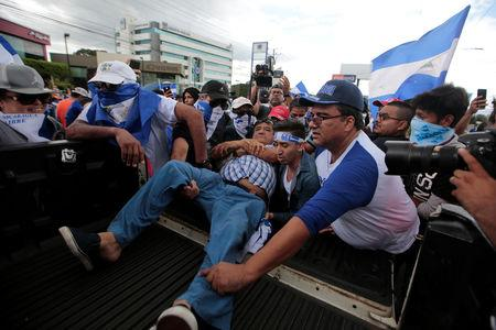Demonstrators help an injured man during a protest against Nicaraguan President Daniel Ortega's government in Managua