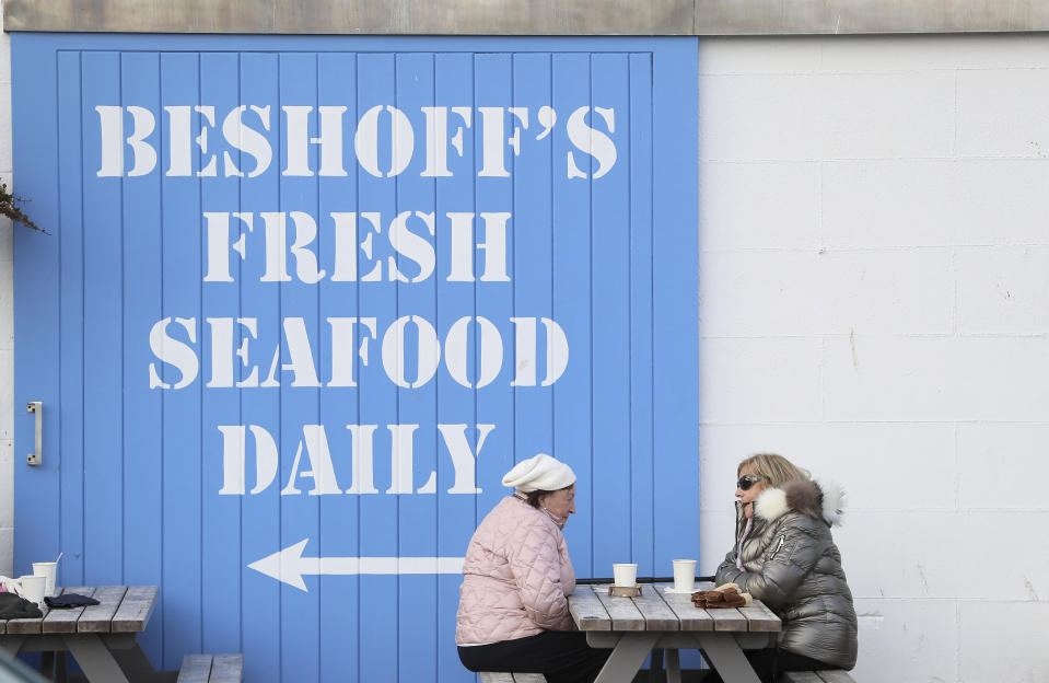 """People sit outside Beshoffs, in the fishing village of Howth, Dublin, Ireland, Thursday, Dec. 17, 2020. Irish coastal communities will be """"annihilated"""" if Britain's post-Brexit fishing demands are granted, an Oireachtas committee has been told. (Brian Lawless/PA via AP)"""