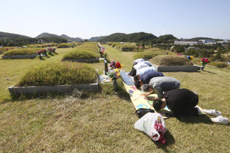 Family members bow to respect at their ancestral cemetery ahead of Chuseok holiday, the Korean version of Thanksgiving Day, at a cemetery in Paju, South Korea, Sunday, Sept. 27, 2020. South Korea's national cemeteries will be closed during the upcoming Chuseok holiday during the five-day holidays from Sept. 30 to Oct. 4 to prevent the spread of the coronavirus. (AP Photo/Ahn Young-joon)