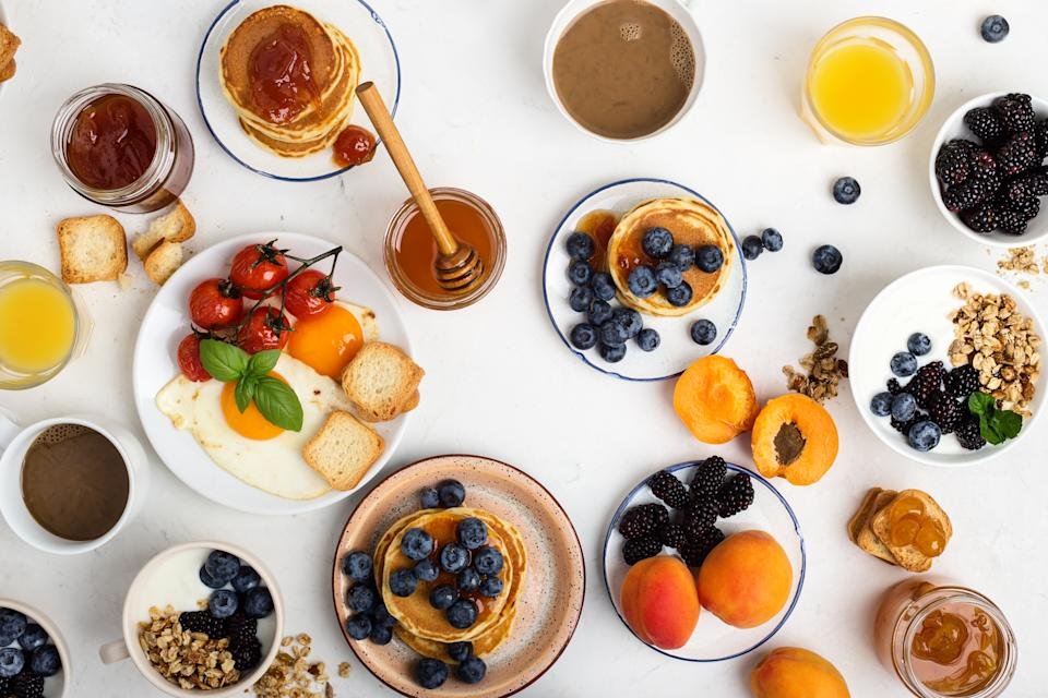 Healthy vegetarian breakfast or brunch, favorite meal. Homemade granola with yoghurt, pancakes, fried eggs, fresh summer fruits, berries, coffee and juice, honey on light gray table viewed from above