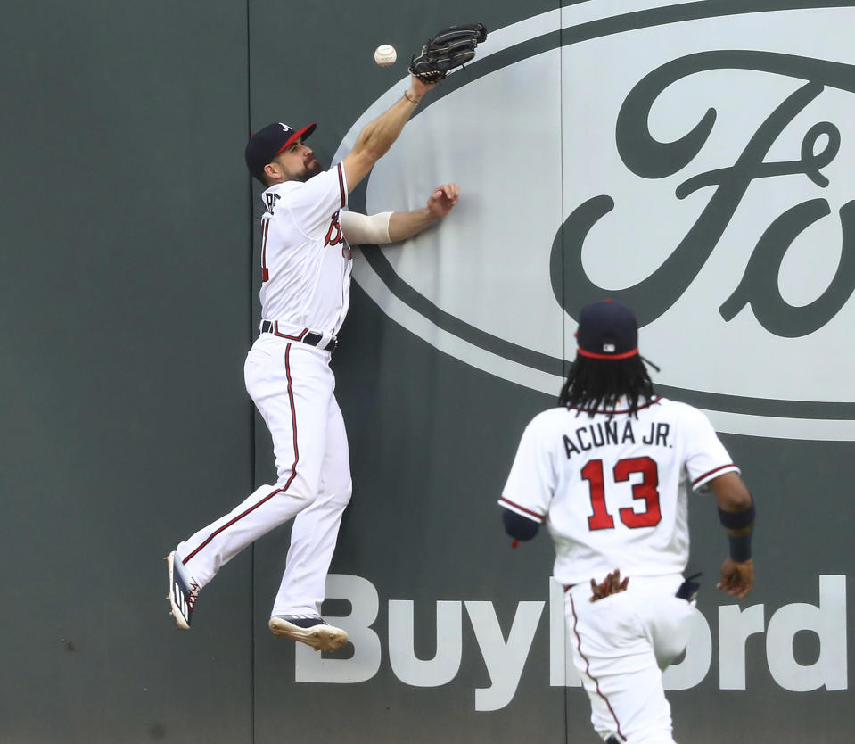 Atlanta Braves center fielder Ender Inciarte just misses a double off the wall by Toronto Blue Jays' Cavan Biggio with right fielder Ronald Acuña watching during the first inning of a baseball game Wednesday, Aug. 5, 2020, in Atlanta. (Curtis Compton/Atlanta Journal-Constitution via AP)