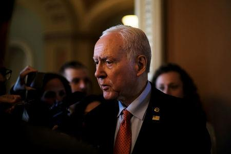 FILE PHOTO: U.S. Senator Orrin Hatch (R-UT) speaks to reporters after leaving the Senate floor during debate over the Republican tax reform plan in Washington, U.S., December 1, 2017. REUTERS/James Lawler Duggan