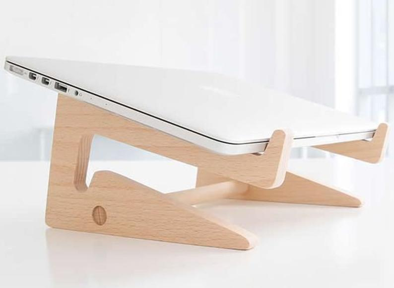 "<h2>Paracel Laptop Wood Stand</h2><br><strong>Best For: Ergonomics</strong><br>This Etsy shop offers multiple wooden laptop stands with the most ergonomic designs. <br><br><em>Shop</em> <strong><em><a href=""https://www.etsy.com/shop/Paracel"" rel=""nofollow noopener"" target=""_blank"" data-ylk=""slk:Paracel"" class=""link rapid-noclick-resp"">Paracel</a></em></strong><br><br><strong>Paracel</strong> Laptop Wood Stand, $, available at <a href=""https://go.skimresources.com/?id=30283X879131&url=https%3A%2F%2Fwww.etsy.com%2Flisting%2F808471877%2Flaptop-wood-stand-laptop-stand-vertical"" rel=""nofollow noopener"" target=""_blank"" data-ylk=""slk:Etsy"" class=""link rapid-noclick-resp"">Etsy</a>"