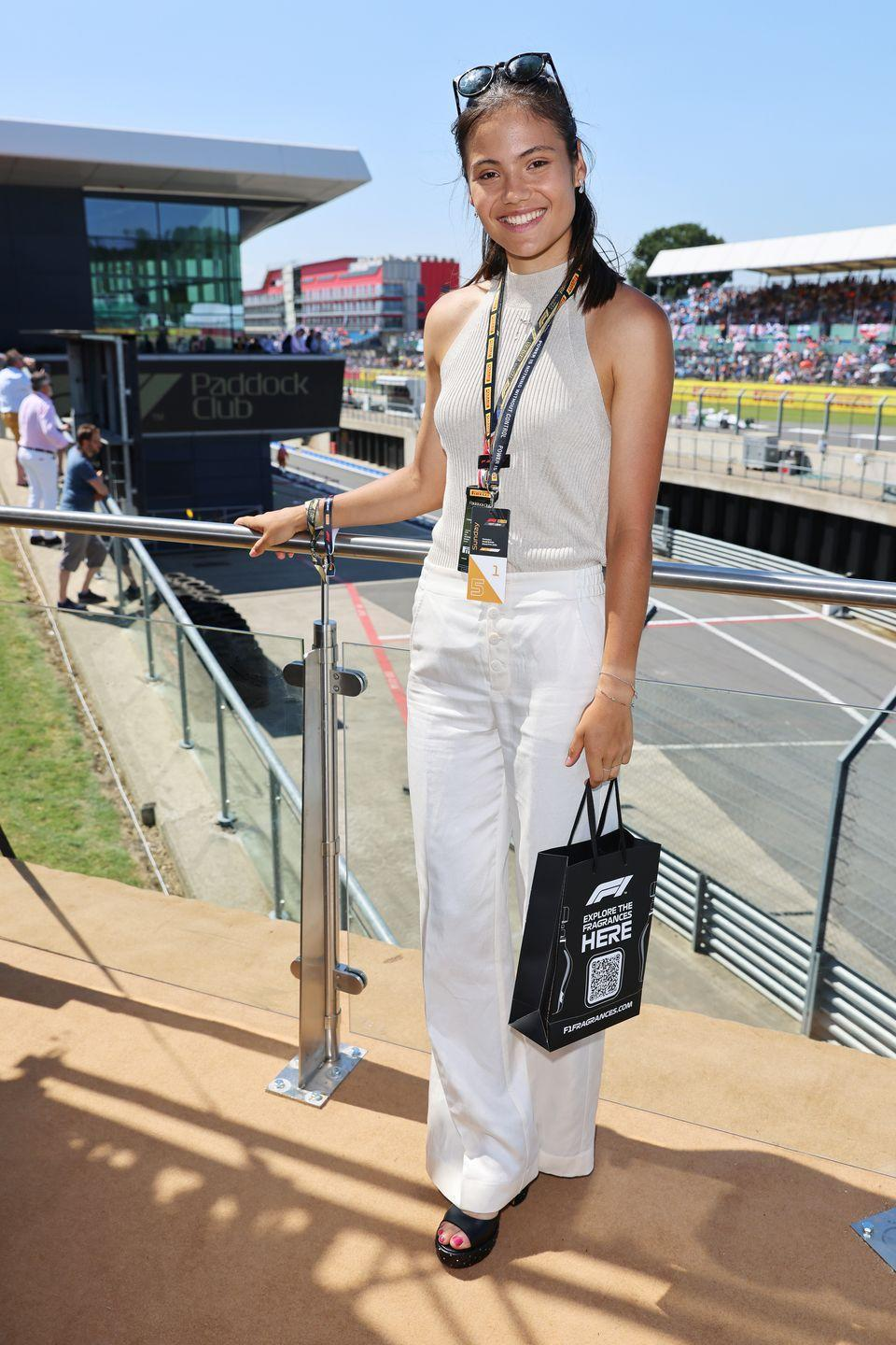 <p>Raducanu soaked up the sunshine dressed in black open-toe sliders, white trousers, a neutral-hued halterneck top and sunglasses. </p>