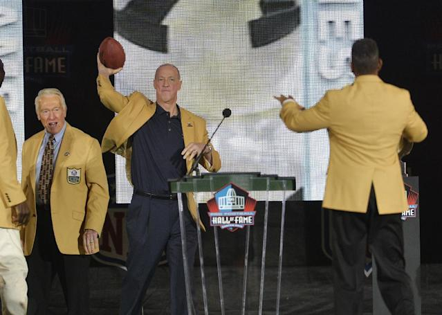 Presenter Marv Levy, left, watches as former Buffalo Bills quarterback Jim Kelly, center, throws a football to inductee Andre Reed during the Pro Football Hall of Fame enshrinement ceremony Saturday, Aug. 2, 2014, in Canton, Ohio. (AP Photo/David Richard)
